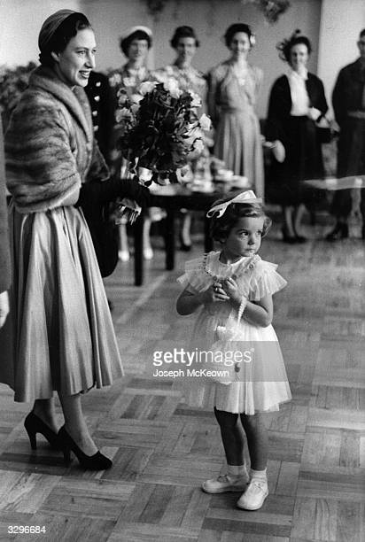 Princess Margaret Rose at the Rhine Centre where she has been given a bouquet by a child of one of the soldiers of the Suffolk regiment The Princess...