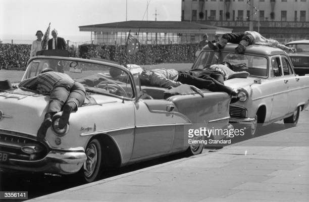 Holiday makers in Clacton-on-Sea relax in the heat by lying on top of their parked cars.