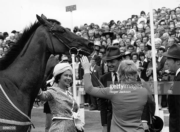 Queen Elizabeth II of Great Britain with her horse 'Highclere' at Epsom racecourse, Surrey.