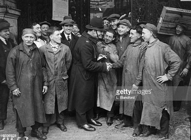 Porters of Smithfield Meat Market in London congratulating PC Titling on his heroism in singlehandedly battling the fire that threatened the market...