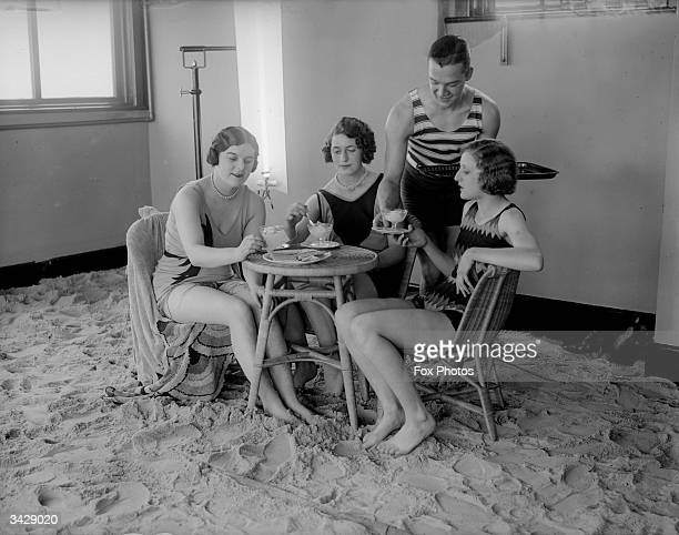 Young waiter serves tea to a group of ladies in the solarium of the Tolland Hotel, Bournemouth.
