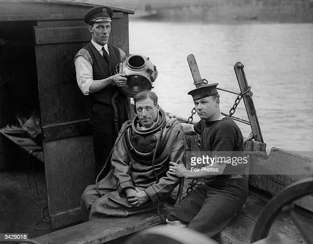 An instructor from Gillingham Diving School helps a man into his diving suit before a lesson in the River Medway Kent