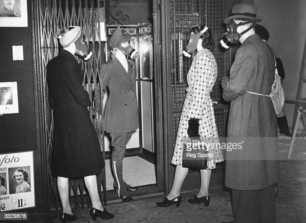 A lift operator and customers at a department store at Bayswater London wearing their gas masks during the store's daily halfhour practice