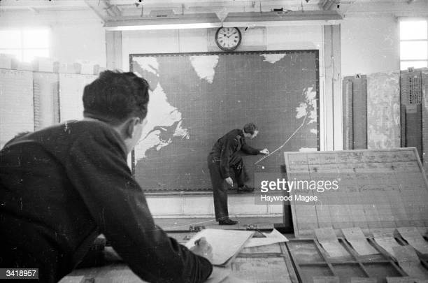 A flight controller at Prestwick Airport charts the progress of a Liberator X 8816 from the Azores to Prestwick on a map of the Atlantic Ocean...