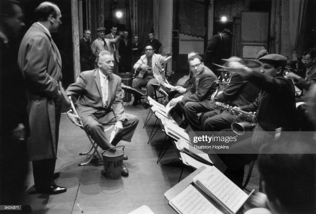 Band leader Stan Kenton rehearses his jazz band at the Stoll Theatre, London, in preparation for a performance at the Albert Hall. Their music is loud, contemporary, ultra-modern jazz, which uses dissonance and organised chaos. Original Publication: Picture Post - 8312 - The Big Noise - pub. 1956