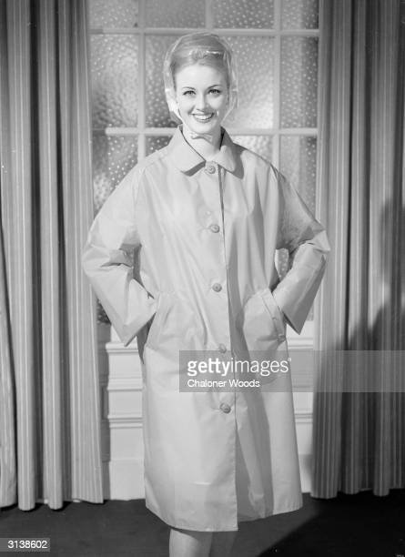 Dressed in a sleeved mackintosh buttoned from neck to hem and with the added precaution of a tie on plastic hood this smiling lady is equipped for a...