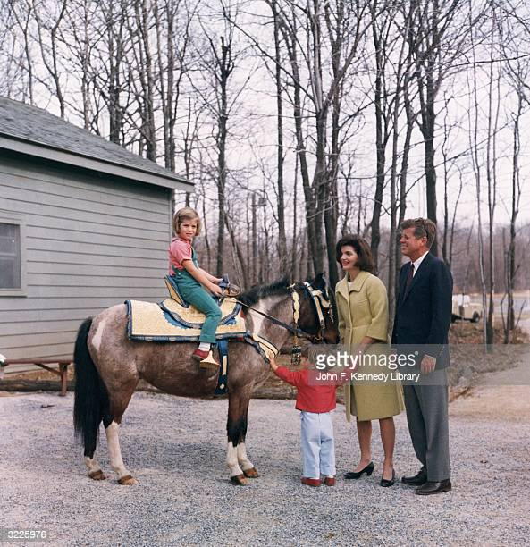 US President John F Kennedy stands outdoors with his wife First Lady Jacqueline Bouvier Kennedy as their daughter Caroline sits atop a pony and their...