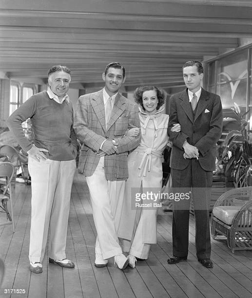 American film actress Joan Crawford off set with director Clarence Brown and actor Clark Gable during the filming of 'Chained'