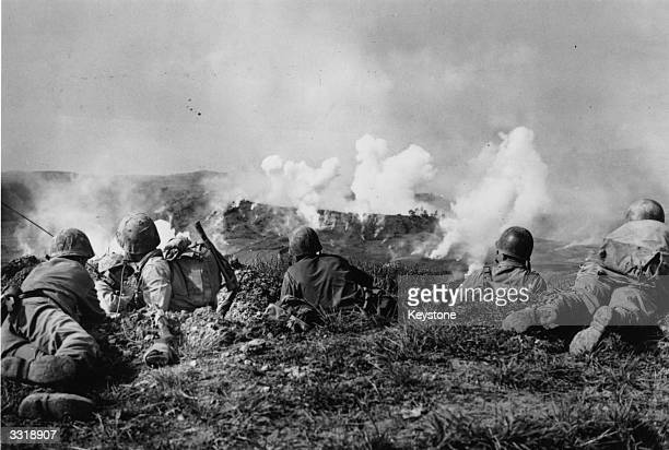 Marines of the 1st Division wait on the crest of a hill in southern Okinawa, as they watch phosphorous shells explode over Japanese soldiers dug into...