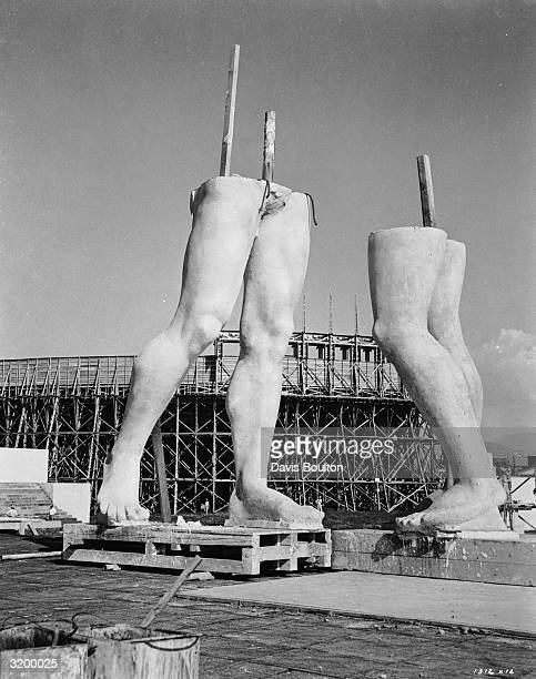 The legs of two massive stone statues being constructed for the Roman epic 'Quo Vadis' directed by Mervyn LeRoy