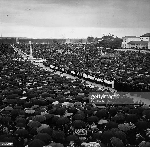 A crowd of pilgrims watching the procession of the Papal Legate in Fatima Portugal where the Virgin Mary is said to have appeared to three children...