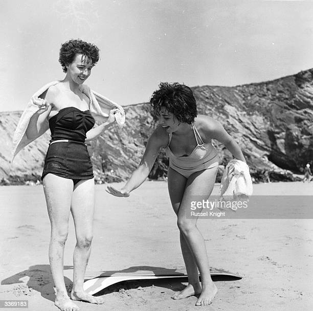 Surfing girls Marilyn Ridge and Dee Delaney dry themselves and their surfboard after shooting a couple of tubes on Newquay beach Cornwall