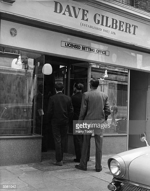 Punters entering a Dave Gilbert bookmaker's in Greville Street London to lay their bets for the Derby Day races
