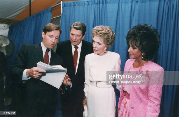 US President Ronald Reagan and First Lady Nancy Reagan look at notes held by an unidentified aide as they stand backstage with American actor...