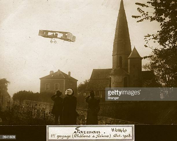 French aviation pioneer Henri Farman flying over a small village near Reims during his European cross country record flight of 26 kilometres from...