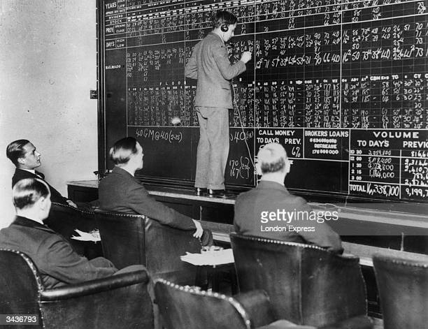In a London club run by St Phalle Ltd members watch fluctuations in the New York stock market during the Wall Street crash as changes are chalked up...