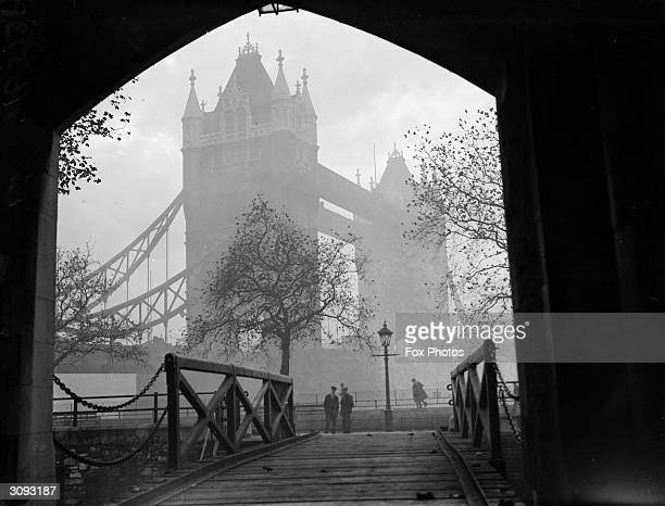 A misty view of London's Tower Bridge seen from an archway in the nearby Tower