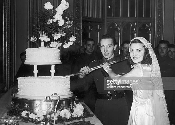 The Earl of Kimberley and his bride Diana Legh cut the wedding cake during their reception in the state drawing rooms of Windsor Castle
