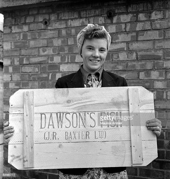 A woman holding a lid of a box which had been full of Icelandic fish shipped to Grimsby England Original Publication Picture Post 6778 I've Bust The...