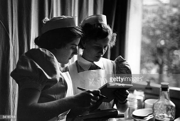 Student nurse Sylvia Maddele checking a patient's chart at the London Hospital Original Publication Picture Post 6780 I Want To Be A Nurse pub 1953