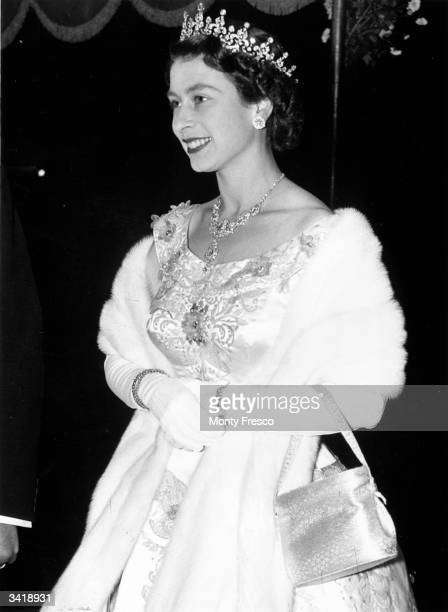 A regally adorned Queen Elizabeth II arriving at the Royal Performance of the film 'To Catch A Thief' at the Odeon Cinema Leicester Square
