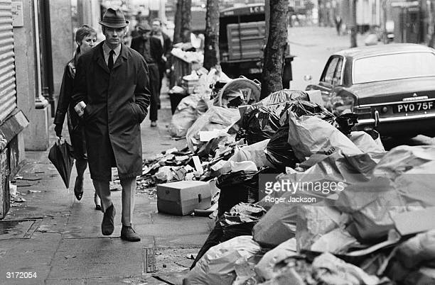 Disgruntled pedestrian walks to work amid piles of rubbish which has accumulated because of a strike by council dustmen.