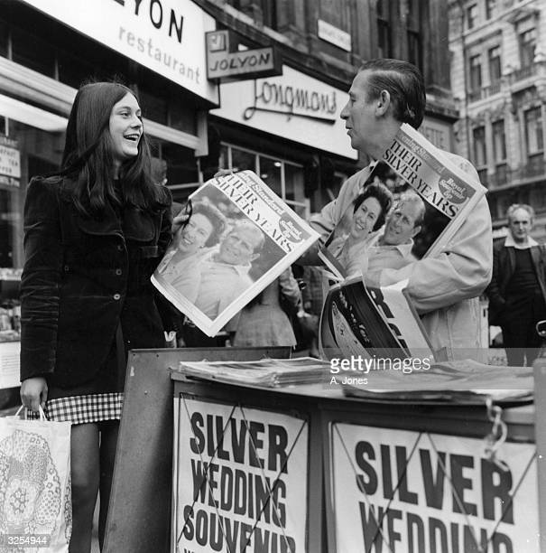 A newspaper vendor sells a copy of the Evening Standard Souvenir Issue of the Queen's Silver Wedding Anniversary to a young lady