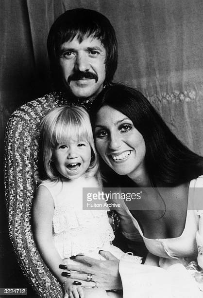 Portrait of married American pop singers and actors Sonny Bono and Cher with their four yearold daughter Chastity