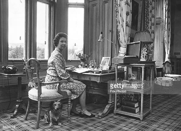 Queen Elizabeth II sitting in her study at Balmoral Castle Scotland dealing with despatch boxes containing State Papers sent from Whitehall