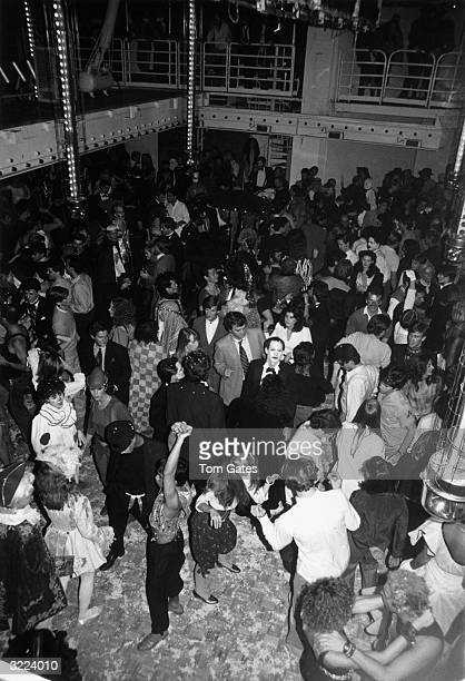 Highangle view of the crowd dancing at Studio 54 in New York City Some dancers wear Halloween costumes
