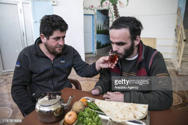 Year-old Syrian Rafid Maguni , who was heavily injured in an airstrike by Assad regime in Syria's Idlib, receives help while having breakfast at a...