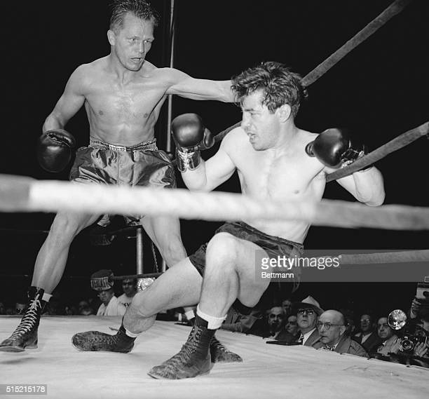 Newark, NJ- Clinging to the Ropes, Rocky Graziano puts up his right arm to ward off a right by Tony Zale, moving in for the kill in the third round...