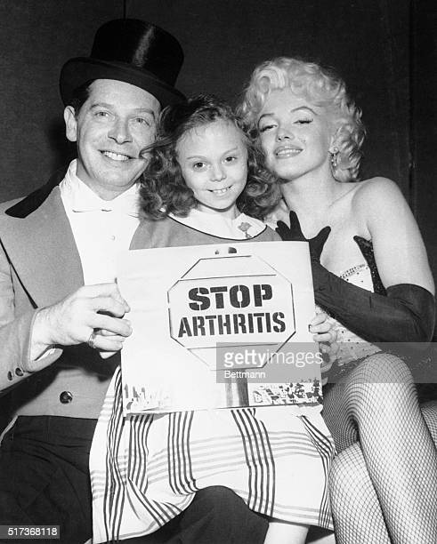 3/22/1955New York NY Marilyn Monroe and Milton Berle pose with 8yearold arthritis poster girl Alice Fitzpatrick during a special precircus...