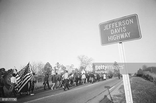 Civil rights marchers one trailing an American flag trudge along US Highway 80 named in honor of the president of the Confederacy as they make their...
