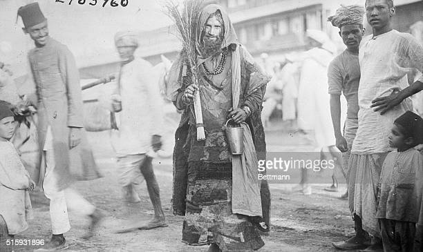 A Mohammedan Fakir at DelhiIn a tattered robe with hood and necklace and a bunch of reeds or feathers
