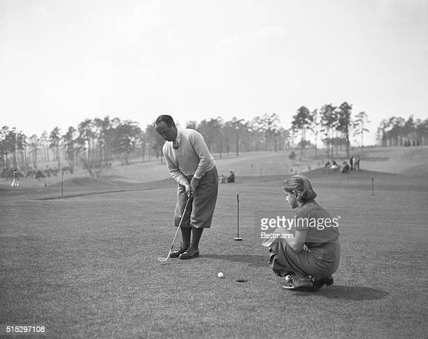 Augusta, GA- Bobby Cruickshank of Richmond, VA., putting during the Masters' Invitation Golf Tournament at Augusta, Georgia, while his daughter,...