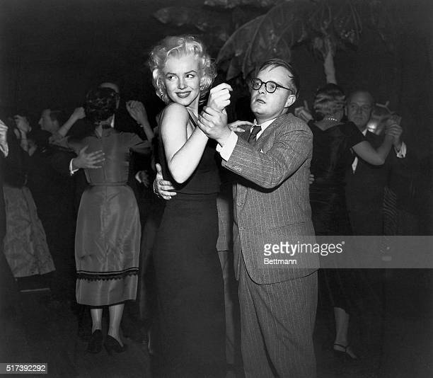 3/24/1955New York NY Novelist Truman Capote seems to be having some difficulty holding the attention of actress Marilyn Monroe while dancing at the...
