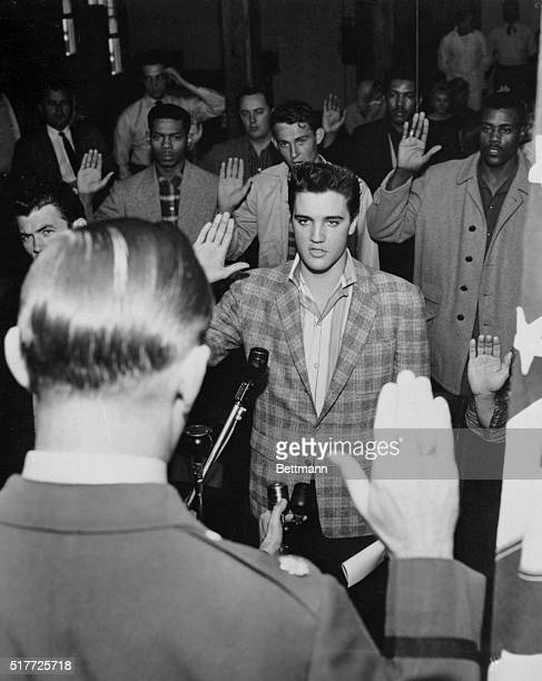 Memphis, Tennessee: Singer Elvis Presley is sworn into the army here March 24th by Maj. Elbert P. Turner . The 23-year old Rock 'N' Roll singing star...