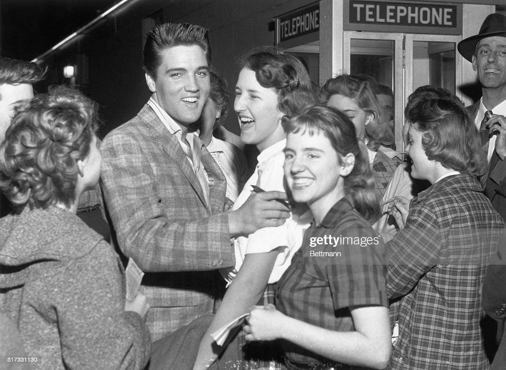 Elvis Presley laughs after an unidentiifed fan asked him