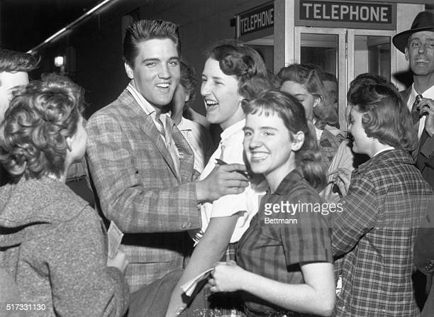 """North Little Rock, Arkansas: Elvis Presley laughs after an unidentiifed fan asked him """"to autograph me,"""" because """"I don't have any pencil and paper.""""..."""
