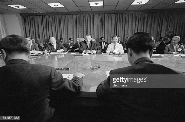 Framed by the shoulders of South Vietnamese leaders Chief of State Lt Gen Nguyen Van Thieu and Premier Nguyen Cao Ky US President Lyndon Johnson...