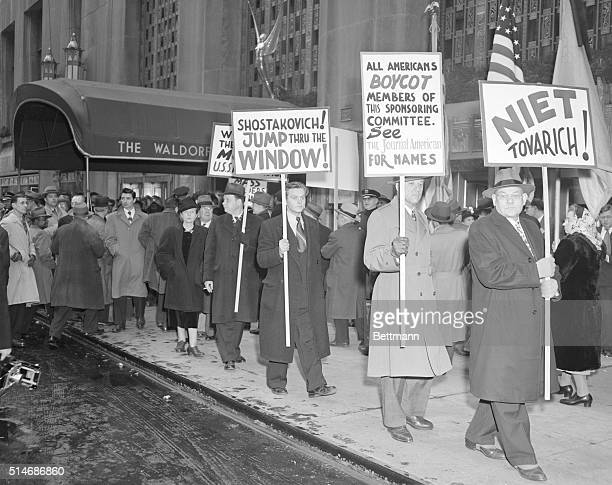 AntiCommunist demonstrators carry placards outside the Waldorf Astoria where a press conference was in progress preceding the opening session of the...
