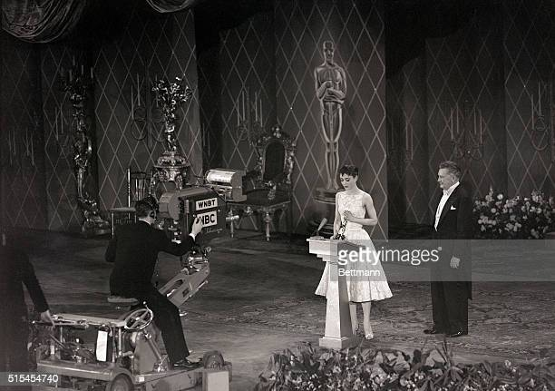 Audrey Hepburn smiles sweetly as she receives Hollywood's highest accoladean Oscar for the best performance by an actressfrom Jean Hersholt at the...