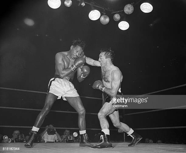 3/25/1958Chicago IL Carmen Basilio his battered left eye closed lands a smashing right to the head of Sugar Ray Robinson in the 11th round of their...