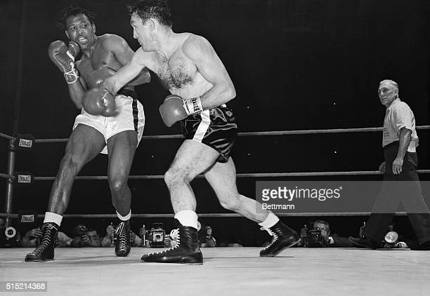3/25/1958Chicago IL Sugar Ray Robinson recoils from a righthand blow by middleweight champion Carmen Basilio during the second round of their title...