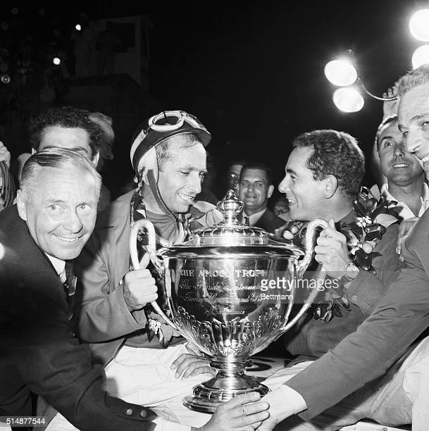 3/25/57Sebring Florida Juan Manuel Fangio left and his partner Jean Behra of France the winning team of the Grand Prix sports car race flash victory...