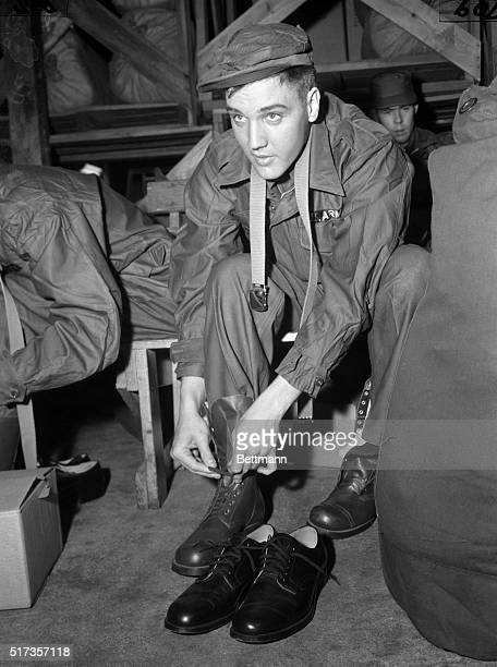 Fort Chaffee, AR: Elvis Presley, idol of a million teenagers, and the Army's property for the next two years, shows off the latest fashion in fatigue...