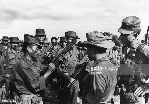 Army Captain Linton Beasley US military advisor trains South Vietnamese rifle squad Beasley is shown here checking rifles before the infantrymen set...