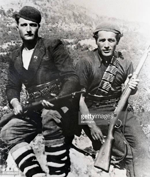 Greece: Two fighters of the Andartes armed with efficient-looking rifles, and wearing makeshift uniforms, are seated atop a rock high in the...
