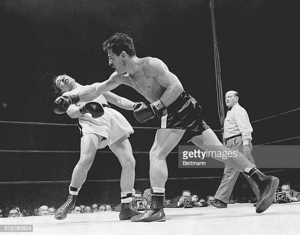 3/31/1950New York NY With referee George Walsh looking on Rocky Graziano is shown following through after landing a hard right in the fifth round of...